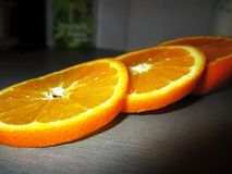 Juicy orange slices close up on grey surface stock photo
