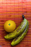 Juicy orange with two speckled bananas on a pink rattan mat background. Negative space for text. Stock Photography