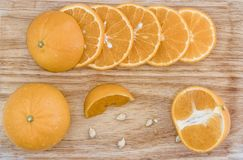 The juicy orange fruit was cut off, saw the fruit pulp on a wooden table. royalty free stock photography
