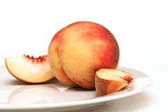 Juicy peach. Slices on a plate with Royalty Free Stock Images