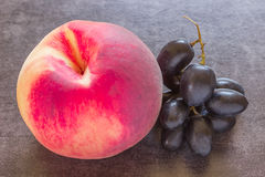 Juicy peach on a black background. Bunch of black grapes. Stock Photo