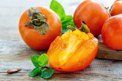 Juicy Persimmon and mint. Royalty Free Stock Photo