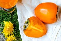 Juicy persimmons και φρέσκος χυμός από πορτοκάλι Στοκ Εικόνα