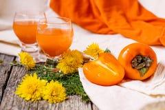 Juicy persimmons και φρέσκος χυμός από πορτοκάλι Στοκ Εικόνες
