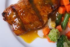 Juicy piece of grilled meat with orange sauce and vegetables Stock Photo