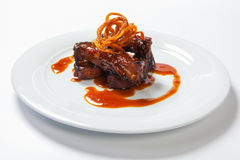 Juicy piece of lamb under red sweet sauce and covered with fried onion on large round white plate on white background. Stock Photography