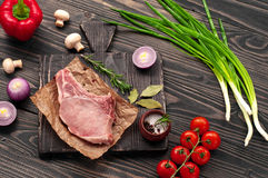Juicy piece of meat on the bone with vegetables Royalty Free Stock Photos