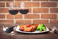 Juicy pieces of grilled meat fillet served with cherry tomatoes branch and lettuce on a white plate, glass of red wine, knife, for Stock Image