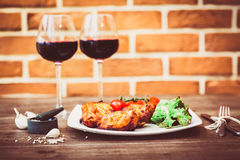 Juicy pieces of grilled meat fillet served with cherry tomatoes branch and lettuce on a white plate, glass of red wine, knife, for Royalty Free Stock Photo
