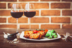 Juicy pieces of grilled meat fillet served with cherry tomatoes branch and lettuce on a white plate, glass of red wine, knife, for Stock Photography