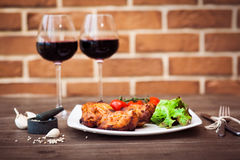 Juicy pieces of grilled meat fillet served with cherry tomatoes branch and lettuce on a white plate, glass of red wine, knife Royalty Free Stock Photos