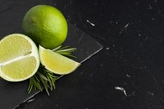 Free Juicy Pieces Of Lime On A Black Marble Board Stock Photography - 122061222