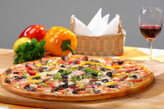 Juicy pizza. Close-up shot pizza and vegetables lying beside her Royalty Free Stock Photos