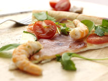 Juicy Pizza slice. PIzza slice with ham, scampi and tomatoes royalty free stock photo