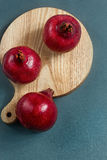 Juicy pomegranate bright red color on the board. On a gray background Royalty Free Stock Image