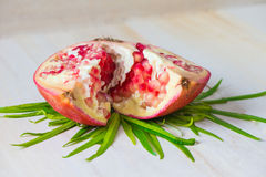 Juicy pomegranate. And its half with leaves royalty free stock photography