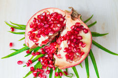 Juicy pomegranate. And its half with leaves royalty free stock photos