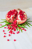 Juicy pomegranate. And its half with leaves royalty free stock photo