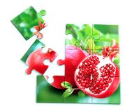 Juicy pomegranate and its half with leaves photo on puzzle boards. With isolated white background Royalty Free Stock Image