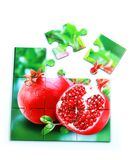 Juicy pomegranate and its half with leaves photo on puzzle boards. With isolated white background Royalty Free Stock Images