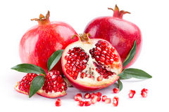 Juicy pomegranate and its half with leaves Royalty Free Stock Photo