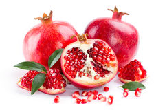 Juicy pomegranate and its half with leaves Stock Photos