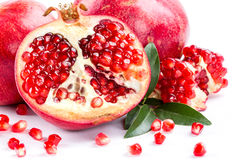 Juicy pomegranate and its half with leaves Royalty Free Stock Photography