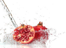 Juicy pomegranate with splashing water Royalty Free Stock Photos