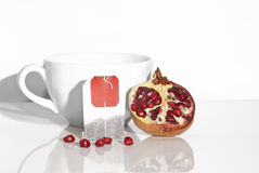 Juicy pomegranate and tea bag Royalty Free Stock Image