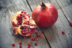 Juicy pomegranates. On wooden background Royalty Free Stock Images