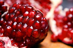 Juicy pomegranates on wooden board Stock Images