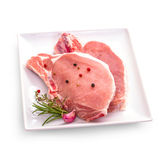 Juicy pork chop, herbs on white plate Royalty Free Stock Photos