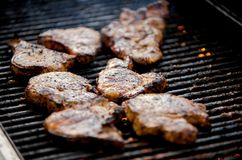 Juicy pork chops on a grill royalty free stock image