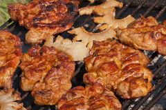 Juicy pork meat and bacon on grill. Juicy pork grill in summer time Royalty Free Stock Image