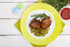 Juicy pork medallions wrapped in bacon, serve with green peas and a sprig of rosemary. On a plate. The top view Royalty Free Stock Image