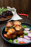 Juicy pork medallions wrapped in bacon, serve on the iron pan Royalty Free Stock Photos