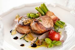 Juicy pork medallions wrapped in bacon, serve on the iron pan on the dark wooden dackground. Close up. stock photography
