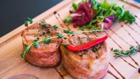 Juicy pork medallions wrapped in bacon, serve on the wooden board stock photo