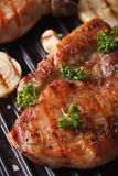 Juicy pork steak grilled in a pan grill macro vertical Royalty Free Stock Image