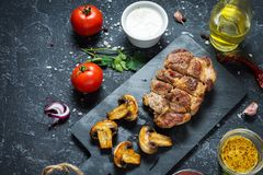 Juicy pork steak with spices and grilled mushroomson dark stone background.  Stock Image