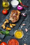 Juicy pork steak with spices and grilled mushroomson dark stone background.  Stock Photo