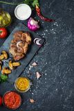 Juicy pork steak with spices and grilled mushroomson dark stone background. Top view. And copy space Royalty Free Stock Photography
