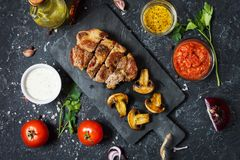 Juicy pork steak with spices and grilled mushroomson dark stone background. Top. View Royalty Free Stock Image