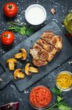 Juicy pork steak with spices and grilled mushroomson dark stone background. Top view Royalty Free Stock Photography