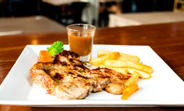 Juicy porkchop on white plate Stock Images