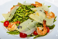 Juicy portions of grilled tiger prawns  with cheese and greens. Stock Photo