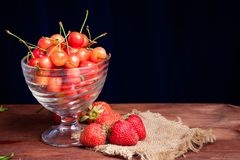 Juicy rainier cherries in a bowl and strawberry. Juicy rainier cherries and strawberry on linen napkin on wooden desk Stock Photo