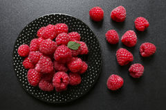 Juicy raspberries on a black background. Juicy raspberries on a plate on black background Stock Photos