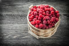 Juicy raspberries in bucket on vintage wooden board.  Stock Images