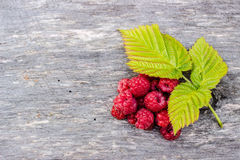 Juicy raspberries lying on wooden table with leaves. Juicy raspberries lying on an old wooden table with three green leaves Stock Photography